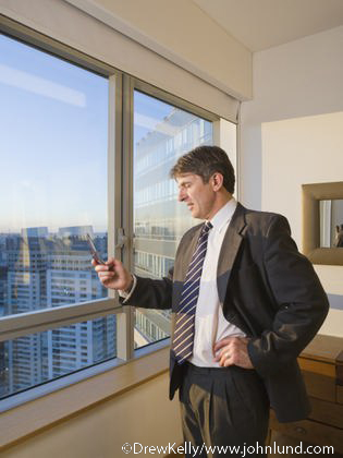 High Rise Apartment Inside man looking at cell phone from inside high rise room